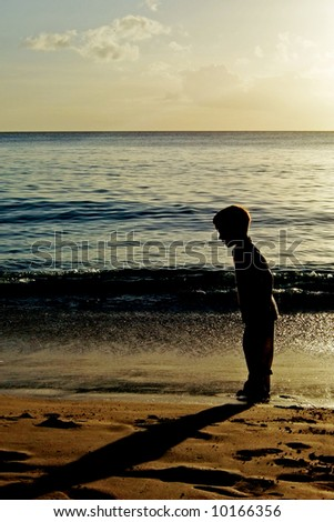 Silhouette of a boy looking at his shadow during a sunset on a beach