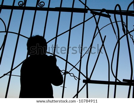 silhouette of a boy near the fence