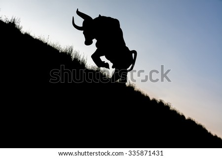 Silhouette of a bull Ramping up the mountain
