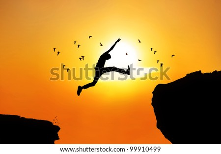 Silhouette of a businessman jumping a wide cliff. Shot outdoor at sunrise - stock photo