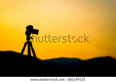 Silhouette of a camera on tripod - stock photo