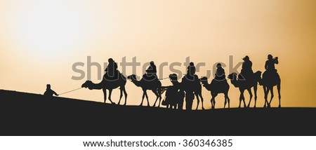 Silhouette of a Caravan of Camels in the Sahara Desert - stock photo