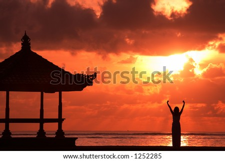 Silhouette of a carefree woman raising her hands enjoying freedom on a tropical beach. Shot in Bali at sunrise - stock photo