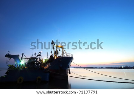 Silhouette of a cargo ship tanker during blue hour immediately after sunset - stock photo