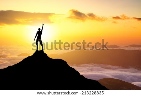 Silhouette of a champion on mountain top. Sport and active life concept  - stock photo