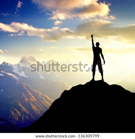 Silhouette of a champion on the high mountain. Sport and active life - stock photo