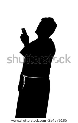 Silhouette of a Christian monk in brown habit - stock photo