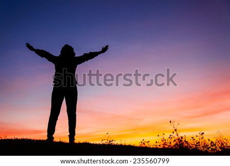 Silhouette of a Christian woman is praying against sunset - stock photo