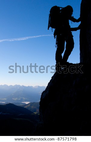 Silhouette of a climber high above valley - stock photo