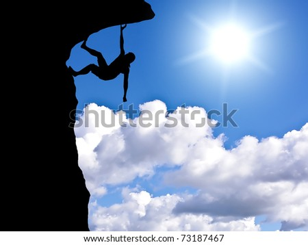silhouette of a climber on a rock against the backdrop of sunny sky - stock photo