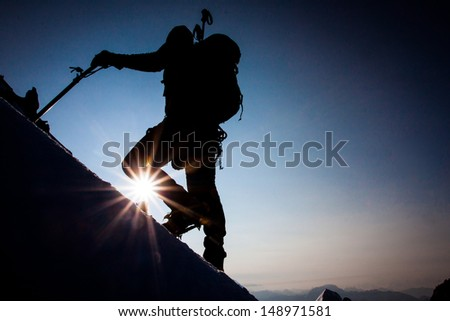 Silhouette of a climber on a steep slope at dawn - stock photo