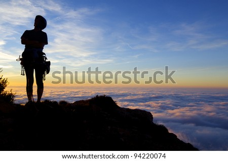 silhouette of a climber with  sunset and sea of ??clouds, Cap of Ras, Ager,  Lleida, Catalonia, Spain - stock photo