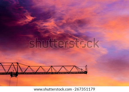 Silhouette of a construction crane at sunset with colorful sky clouds - stock photo
