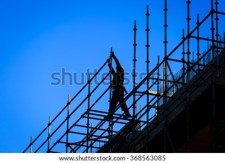 Silhouette of a construction worker and a blue sky. - stock photo