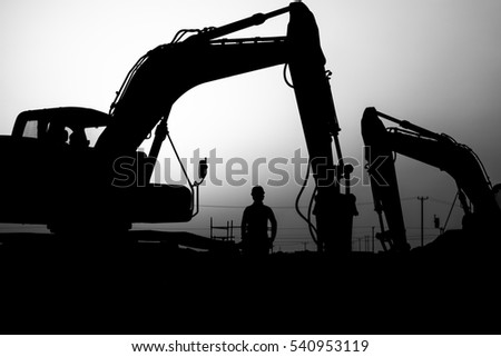 silhouette of a construction worker and  excavator in oilfield - black and white