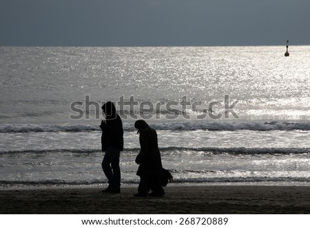 Silhouette of a couple at sunrise walking along beach - stock photo