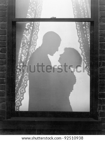 Silhouette of a couple embracing - stock photo