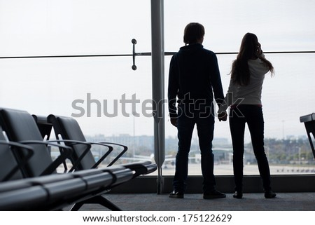 Silhouette of a couple holding hands and waiting at airport terminal - stock photo