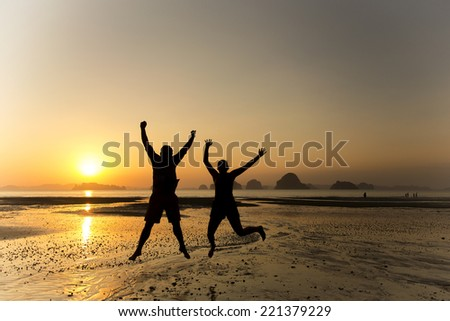 Silhouette of a couple jumping on the beach sunset in Krabi, Thailand