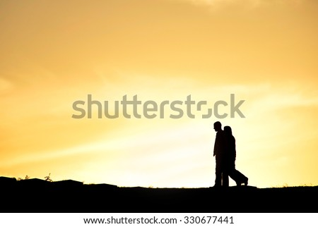 SIlhouette of a couple walking at sunset on a hill - stock photo