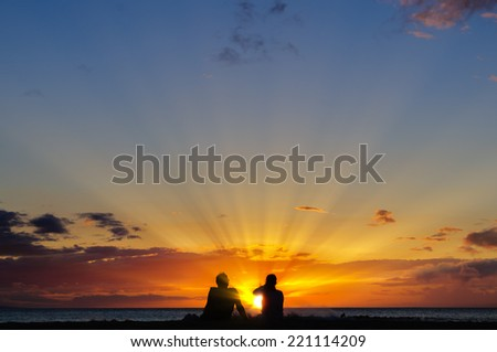 Silhouette of a couple watching a colorful sunset on a beach in Maui, Hawaii, USA - stock photo