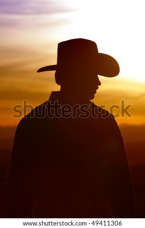 Silhouette of a cowboy backlit against a bright and colorful sunset sky (high contrast).