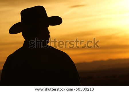 Silhouette of a cowboy backlit against a bright and colorful sunset sky (high contrast). - stock photo