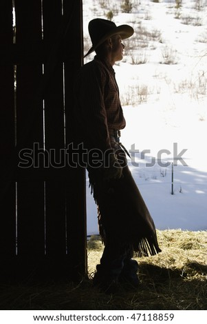 Silhouette of a cowboy leaning in a barn doorway, looking outside. Vertical shot. - stock photo