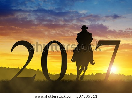 Silhouette of a cowboy riding a horse in the sunset. Forward to the New Year 2017