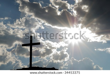 Silhouette of a cross with bright sun - stock photo