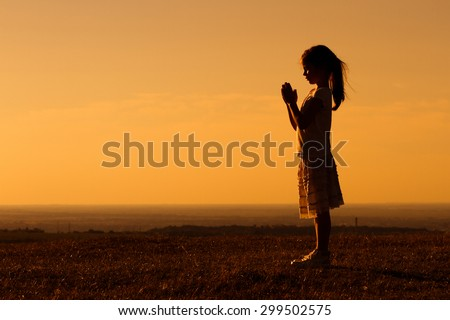 Silhouette of a cute little girl meditating.Little girl meditating - stock photo
