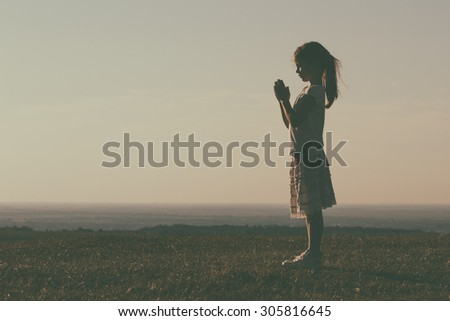 Silhouette of a cute little girl meditating.Little girl meditating Image is intentionally with grain and toned. - stock photo