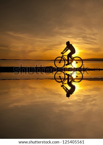 silhouette of a cyclist at sunset with a blurred reflection in the water with ripples - stock photo