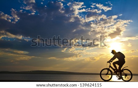 silhouette of a cyclist at sunset with a blurred reflection in the water with ripples