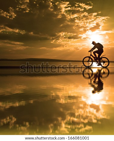 silhouette of a cyclist at sunset with a blurred reflection in the water with ripples on yellow cloudy sun set sky background Copy space for inscription