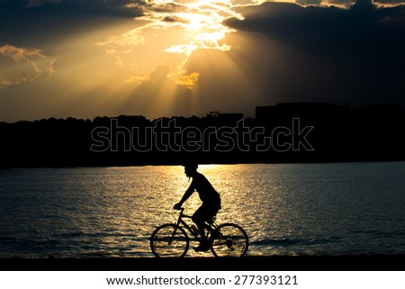 Silhouette of a cyclist in a dramatic clouds background - Washington DC, Potomac Riverside - stock photo
