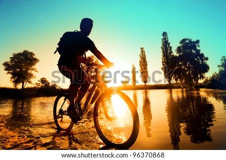 silhouette of a cyclist near the river Irpen, Kiev, Ukraine - stock photo