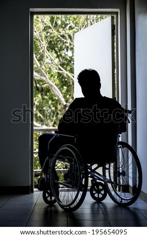 Silhouette of a depressed disabled man sitting on a wheelchair looking out on an open door. - stock photo