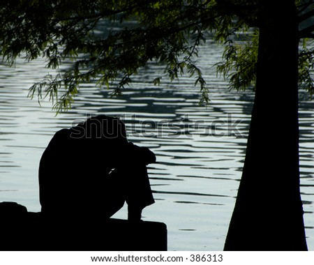 Silhouette of a depressed man by the lake - stock photo