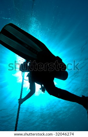 Silhouette of a diver hanging on a rope - stock photo