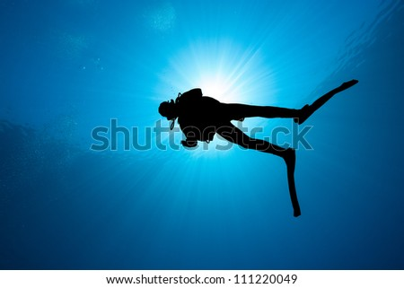 Silhouette of a diver with bubbles and a sunburst - stock photo