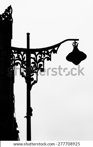 Silhouette of a elegant street lamp. Wrought iron of flower shapes on lamp post. - stock photo