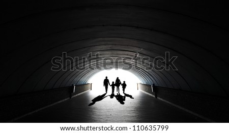 Silhouette of a family comprising the father, mother and two children walking into the light at the end of an underground tunnel.