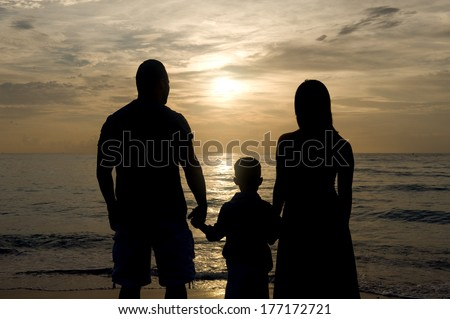 Silhouette of a family of three holding hands watching the sunrise  - stock photo