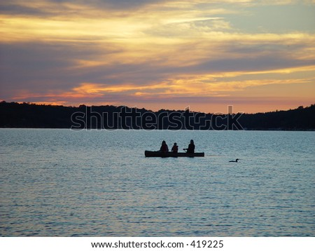 silhouette of a family of three in a kayak on a lake in ontario, canada at sunset - stock photo