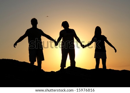 Silhouette of a family on a rock by the sea