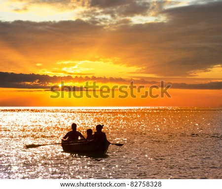 Silhouette of a family that travels on a boat at sunset. - stock photo