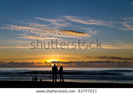 Silhouette of a family watching the sunset at a beach - stock photo
