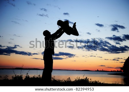 Silhouette of a father lifting up his daughter in the sunset - stock photo