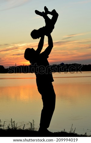 Silhouette of a father playing with baby on sunset background - stock photo